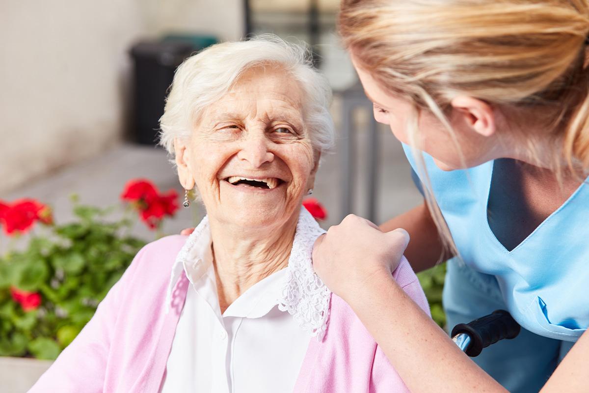 Szene bei der alters- und bedarfsgerechten Pflege mit glücklicher Seniorin